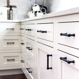 Mid-sized farmhouse enclosed kitchen appliance - Inspiration for a mid-sized country l-shaped medium tone wood floor and brown floor enclosed kitchen remodel in Columbus with a farmhouse sink, flat-panel cabinets, white cabinets, quartzite countertops, white backsplash, marble backsplash, stainless steel appliances, an island and white countertops