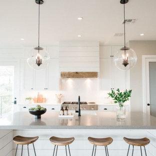 Idéer för mellanstora lantliga linjära vitt kök med öppen planlösning, med en rustik diskho, skåp i shakerstil, vita skåp, bänkskiva i kvartsit, vitt stänkskydd, stänkskydd i marmor, rostfria vitvaror, ljust trägolv, en köksö och brunt golv
