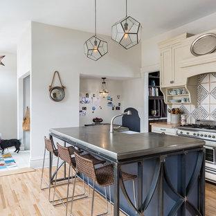 Inspiration för lantliga kök, med en rustik diskho, luckor med infälld panel, beige skåp, träbänkskiva, flerfärgad stänkskydd, stänkskydd i keramik, integrerade vitvaror, ljust trägolv och en köksö