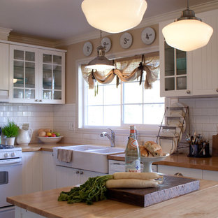 Inspiration for a mid-sized traditional l-shaped eat-in kitchen in Los Angeles with subway tile splashback, a farmhouse sink, wood benchtops, glass-front cabinets, white cabinets, white splashback, white appliances, with island and vinyl floors.