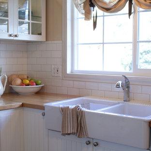 ロサンゼルスの中サイズのトラディショナルスタイルのおしゃれなキッチン (エプロンフロントシンク、ガラス扉のキャビネット、白いキャビネット、木材カウンター、白いキッチンパネル、サブウェイタイルのキッチンパネル、白い調理設備、クッションフロア) の写真