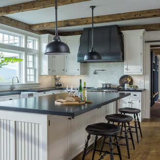 Mid-sized farmhouse kitchen designs - Mid-sized cottage u-shaped medium tone wood floor and brown floor kitchen photo in Other with a farmhouse sink, white cabinets, granite countertops, white backsplash, subway tile backsplash, stainless steel appliances, an island, black countertops and beaded inset cabinets