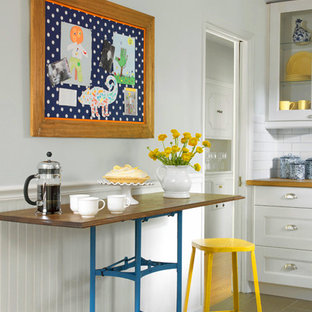 Small country galley eat-in kitchen in St Louis with a farmhouse sink, shaker cabinets, white cabinets, wood benchtops, white splashback, subway tile splashback, stainless steel appliances, porcelain floors and with island.
