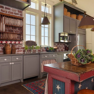Cottage single-wall concrete floor kitchen photo in Houston with shaker cabinets, gray cabinets, red backsplash, stainless steel appliances, an island and wood countertops