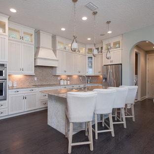Design ideas for a mid-sized country single-wall eat-in kitchen in Jacksonville with a double-bowl sink, louvered cabinets, white cabinets, marble benchtops, beige splashback, stone tile splashback, stainless steel appliances, vinyl floors and with island.