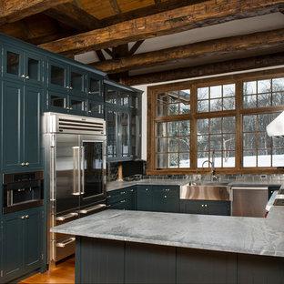 Inredning av ett rustikt avskilt, stort u-kök, med luckor med profilerade fronter, gröna skåp, bänkskiva i täljsten, stänkskydd med metallisk yta, stänkskydd i metallkakel, rostfria vitvaror, ljust trägolv och en rustik diskho
