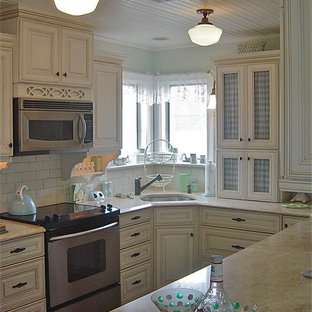 This is an example of a mid-sized country u-shaped separate kitchen in Other with a drop-in sink, raised-panel cabinets, beige cabinets, limestone benchtops, beige splashback, ceramic splashback and stainless steel appliances.