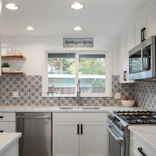 Mid-sized farmhouse enclosed kitchen photos - Enclosed kitchen - mid-sized country l-shaped enclosed kitchen idea in Seattle with an undermount sink, shaker cabinets, white cabinets, quartz countertops, gray backsplash, ceramic backsplash, stainless steel appliances, no island and white countertops