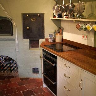 他の地域の中サイズのトラディショナルスタイルのおしゃれなキッチン (シェーカースタイル扉のキャビネット、白いキャビネット、木材カウンター、黒い調理設備、テラコッタタイルの床、アイランドなし、赤い床、茶色いキッチンカウンター) の写真