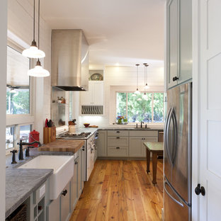 Design ideas for a country kitchen in Austin with stainless steel appliances, a farmhouse sink and soapstone benchtops.