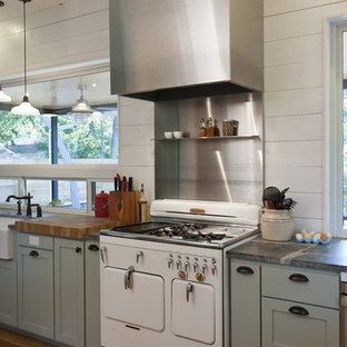 Farmhouse kitchen inspiration - Example of a cottage kitchen design in Austin with white appliances, metal backsplash, metallic backsplash, gray cabinets, shaker cabinets and a farmhouse sink
