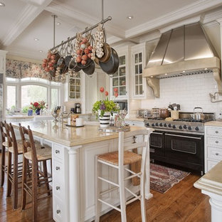 Eat-in kitchen - large traditional u-shaped medium tone wood floor eat-in kitchen idea in San Francisco with stainless steel appliances, a farmhouse sink, beaded inset cabinets, white cabinets, limestone countertops, white backsplash, ceramic backsplash and an island