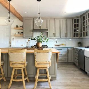 Photo of a small country l-shaped open plan kitchen in Los Angeles with raised-panel cabinets, grey cabinets, with island, a farmhouse sink, quartz benchtops, white splashback, subway tile splashback, stainless steel appliances, light hardwood floors, beige floor and white benchtop.