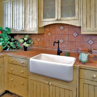 Idéer för ett mellanstort medelhavsstil kök, med en rustik diskho, luckor med profilerade fronter, gula skåp, marmorbänkskiva, flerfärgad stänkskydd, stänkskydd i terrakottakakel och klinkergolv i terrakotta