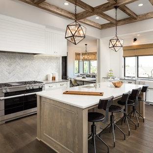 Große Landhausstil Küche in U-Form mit Landhausspüle, flächenbündigen Schrankfronten, weißen Schränken, Quarzwerkstein-Arbeitsplatte, Küchenrückwand in Weiß, Kalk-Rückwand, Küchengeräten aus Edelstahl, dunklem Holzboden, Kücheninsel und braunem Boden in Orange County