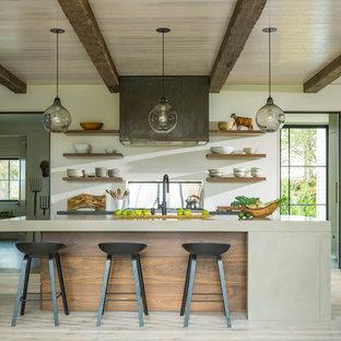 バーリントンの中サイズのカントリー風おしゃれなキッチン (アンダーカウンターシンク、フラットパネル扉のキャビネット、ベージュのキャビネット、コンクリートカウンター、白いキッチンパネル、磁器タイルのキッチンパネル、シルバーの調理設備の、淡色無垢フローリング、ベージュのキッチンカウンター、ベージュの床) の写真