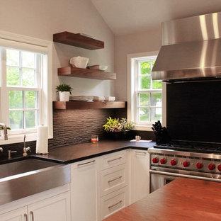 ボストンの中サイズのカントリー風おしゃれなキッチン (エプロンフロントシンク、シェーカースタイル扉のキャビネット、白いキャビネット、人工大理石カウンター、黒いキッチンパネル、磁器タイルのキッチンパネル、パネルと同色の調理設備、セラミックタイルの床、黒い床) の写真