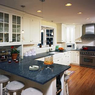 Idéer för lantliga blått kök, med luckor med glaspanel, en rustik diskho, vita skåp, bänkskiva i täljsten, vitt stänkskydd, stänkskydd i tunnelbanekakel och rostfria vitvaror