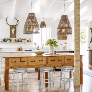 Small farmhouse kitchen designs - Small cottage light wood floor kitchen photo in Los Angeles with a farmhouse sink, white cabinets, quartz countertops, white backsplash, stainless steel appliances, an island and shaker cabinets