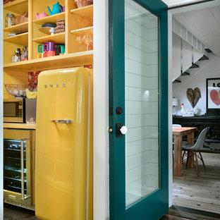 Foto di una cucina country chiusa con lavello da incasso, ante gialle, top in quarzo composito, paraspruzzi bianco, parquet scuro, pavimento marrone e top giallo