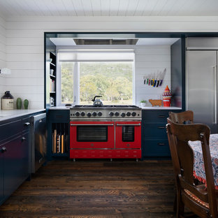 This is an example of a country separate kitchen in Austin with a drop-in sink, turquoise cabinets, quartz benchtops, white splashback, dark hardwood floors, brown floor and yellow benchtop.