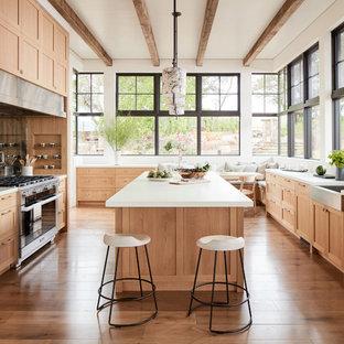 Modelo de cocina campestre con fregadero sobremueble, armarios estilo shaker, puertas de armario de madera clara, electrodomésticos de acero inoxidable, suelo de madera en tonos medios, una isla y encimeras blancas