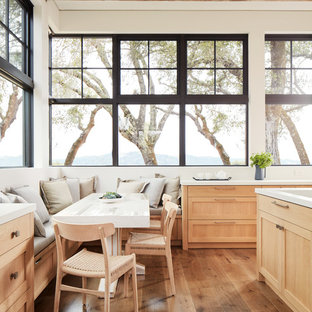 Example of a farmhouse medium tone wood floor eat-in kitchen design in San Francisco with shaker cabinets, light wood cabinets and white countertops