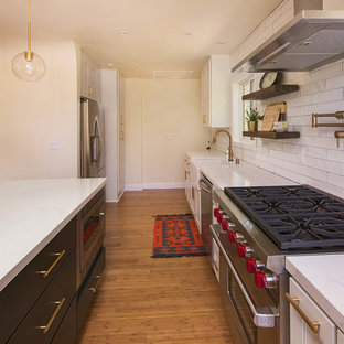 This is an example of a medium sized country single-wall open plan kitchen in Los Angeles with a belfast sink, shaker cabinets, white cabinets, engineered stone countertops, white splashback, porcelain splashback, stainless steel appliances, light hardwood flooring, an island, brown floors and yellow worktops.