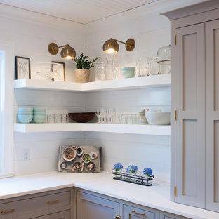 Réalisation d'une cuisine champêtre en U avec un placard à porte plane, des portes de placard grises, une crédence blanche, un électroménager en acier inoxydable, un sol en bois clair et un îlot central.
