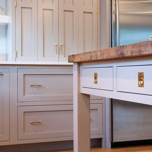Imagen de cocina en U, campestre, con armarios con paneles lisos, puertas de armario grises, salpicadero blanco, electrodomésticos de acero inoxidable, suelo de madera clara y una isla