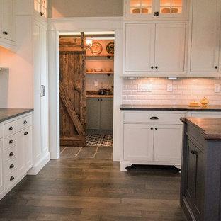 ボストンの大きいカントリー風おしゃれなキッチン (エプロンフロントシンク、落し込みパネル扉のキャビネット、白いキャビネット、人工大理石カウンター、グレーのキッチンパネル、サブウェイタイルのキッチンパネル、シルバーの調理設備の、濃色無垢フローリング) の写真