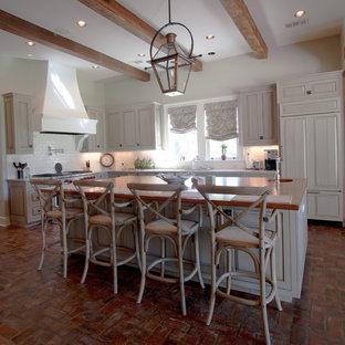 ニューオリンズの広いカントリー風おしゃれなキッチン (インセット扉のキャビネット、白いキャビネット、御影石カウンター、白いキッチンパネル、サブウェイタイルのキッチンパネル、パネルと同色の調理設備、レンガの床、赤い床) の写真