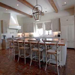 This is an example of a large farmhouse l-shaped kitchen in New Orleans with beaded cabinets, an island, white cabinets, granite worktops, white splashback, metro tiled splashback, integrated appliances, brick flooring and red floors.