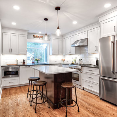 Inspiration for a mid-sized country l-shaped brown floor and medium tone wood floor kitchen remodel in New York with white cabinets, white backsplash, subway tile backsplash, stainless steel appliances, an island, black countertops, an undermount sink, shaker cabinets and soapstone countertops