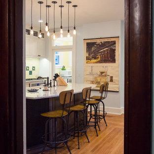 Geschlossene, Große Country Küche in U-Form mit Landhausspüle, Schrankfronten im Shaker-Stil, weißen Schränken, Granit-Arbeitsplatte, Küchenrückwand in Gelb, Rückwand aus Terrakottafliesen, bunten Elektrogeräten, braunem Holzboden und Kücheninsel in Cincinnati