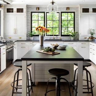Неиссякаемый источник вдохновения для домашнего уюта: п-образная, отдельная кухня среднего размера в стиле кантри с врезной раковиной, фасадами в стиле шейкер, столешницей из гранита, серым фартуком, цветной техникой, светлым паркетным полом, островом, коричневым полом, белыми фасадами, фартуком из удлиненной плитки и черной столешницей