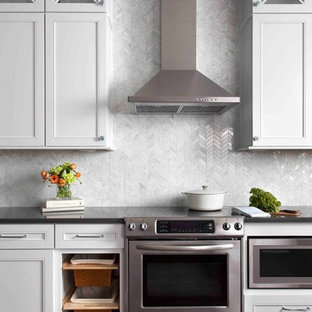 Design ideas for a large transitional eat-in kitchen in Austin with white cabinets, stone tile splashback, stainless steel appliances, dark hardwood floors, shaker cabinets, solid surface benchtops, white splashback, brown floor, black benchtop and with island.