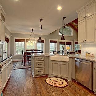 アトランタの中サイズのカントリー風おしゃれなキッチン (エプロンフロントシンク、落し込みパネル扉のキャビネット、グレーのキャビネット、白いキッチンパネル、サブウェイタイルのキッチンパネル、シルバーの調理設備の、無垢フローリング、御影石カウンター、茶色い床、ベージュのキッチンカウンター) の写真