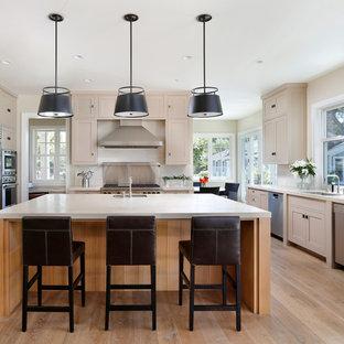 Diseño de cocina comedor en U, de estilo de casa de campo, con fregadero bajoencimera, armarios estilo shaker, puertas de armario beige, salpicadero blanco, electrodomésticos de acero inoxidable y salpicadero de piedra caliza
