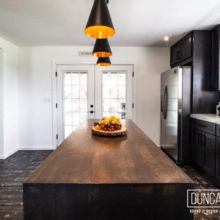 Réalisation d'une cuisine américaine parallèle minimaliste de taille moyenne avec un évier encastré, un placard à porte shaker, des portes de placard en bois sombre, un plan de travail en béton, une crédence métallisée, une crédence en dalle métallique, un électroménager en acier inoxydable, un sol en bambou, un îlot central, un sol gris et un plan de travail gris.