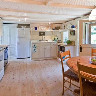 Inspiration for a medium sized farmhouse l-shaped kitchen/diner in Philadelphia with an integrated sink, flat-panel cabinets, white cabinets, wood worktops, white splashback, stainless steel appliances, plywood flooring, wood splashback, no island, beige floors and brown worktops.