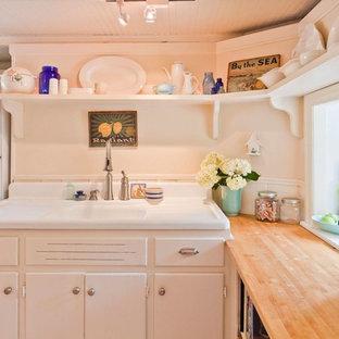 Inspiration för ett mellanstort lantligt brun brunt kök, med en integrerad diskho, släta luckor, vita skåp, träbänkskiva, vitt stänkskydd, stänkskydd i trä, rostfria vitvaror, plywoodgolv och beiget golv