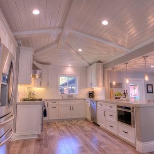 サクラメントの中サイズのカントリー風おしゃれなキッチン (シングルシンク、フラットパネル扉のキャビネット、白いキャビネット、クオーツストーンカウンター、白いキッチンパネル、セラミックタイルのキッチンパネル、シルバーの調理設備の、無垢フローリング、グレーの床、グレーのキッチンカウンター) の写真
