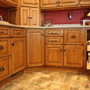 Small farmhouse eat-in kitchen ideas - Example of a small country u-shaped vinyl floor eat-in kitchen design in Milwaukee with an undermount sink, raised-panel cabinets, medium tone wood cabinets, granite countertops, red backsplash, wood backsplash, white appliances and an island