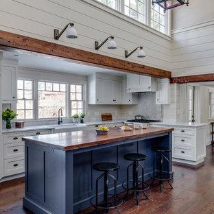 Offene, Große Landhausstil Küche in L-Form mit Landhausspüle, Marmor-Arbeitsplatte, Kücheninsel, braunem Boden, Schrankfronten im Shaker-Stil, blauen Schränken, Elektrogeräten mit Frontblende, braunem Holzboden, weißer Arbeitsplatte, Küchenrückwand in Grau und Rückwand aus Marmor in Boston