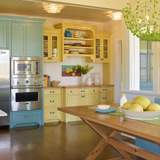 Design ideas for a country eat-in kitchen in San Francisco with yellow cabinets, wood benchtops, stainless steel appliances and dark hardwood floors.