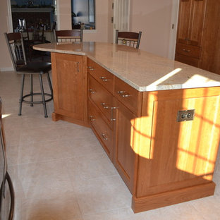 Traditional eat-in kitchen appliance - Eat-in kitchen - traditional l-shaped eat-in kitchen idea in Boston with an undermount sink, recessed-panel cabinets, light wood cabinets, granite countertops and stainless steel appliances