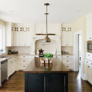 Traditional kitchen inspiration - Elegant kitchen photo in Vancouver with granite countertops, stainless steel appliances and travertine backsplash