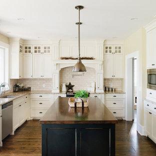 Réalisation d'une cuisine tradition avec un plan de travail en granite, un électroménager en acier inoxydable et une crédence en travertin.