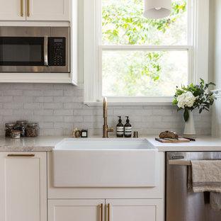 サンフランシスコの小さいトランジショナルスタイルのおしゃれなキッチン (白いキャビネット、白いキッチンパネル、レンガのキッチンパネル、シルバーの調理設備の、淡色無垢フローリング、アイランドなし、ベージュの床、ベージュのキッチンカウンター) の写真